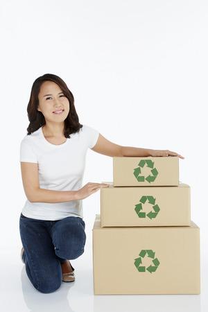 Woman kneeling beside a stack of cardboard boxes