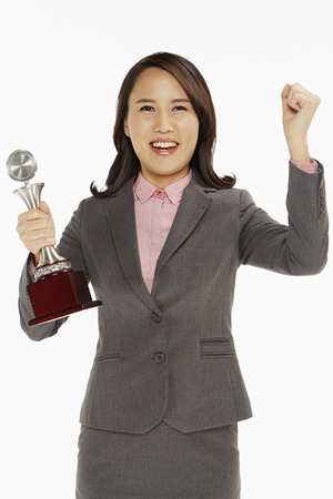 Businesswoman holding a trophy and cheering photo