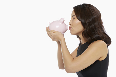 puckering lips: Woman kissing a piggy bank