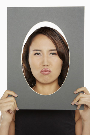 puckering lips: Woman holding up an oval frame