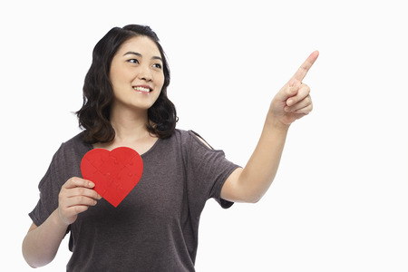 Cheerful woman holding up a red heart shape photo