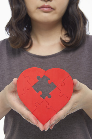 Sad woman holding up a red heart shape with a missing puzzle piece photo