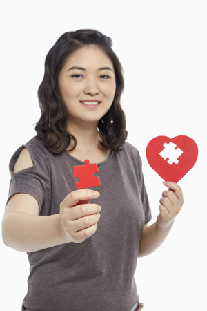 Woman holding a puzzle piece from a heart shape photo