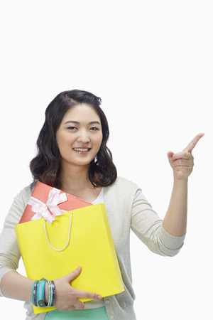 Woman with paper bag pointing to the left photo