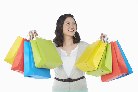Happy woman holding up colorful paper bags photo