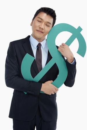 Businessman embracing a dollar sign photo