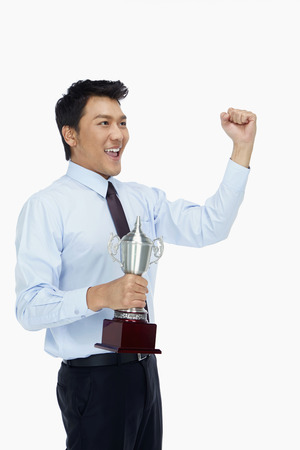 Businessman holding a trophy and cheering photo
