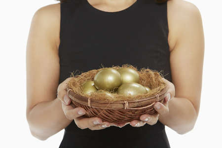 Woman holding a nest filled with golden eggs photo