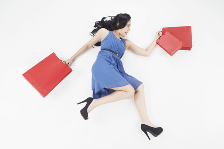 Woman posing on the ground while carrying shopping bags photo