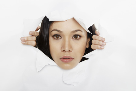 Woman looking through a torn paper