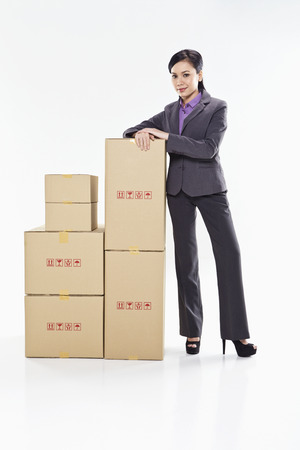 Businesswoman standing beside a stack of boxes photo
