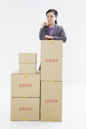 Businesswoman standing behind a stack of boxes photo