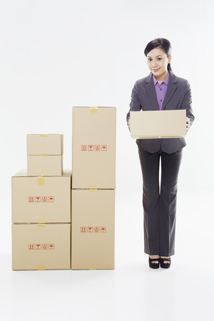 Businesswoman holding out a cardboard box photo