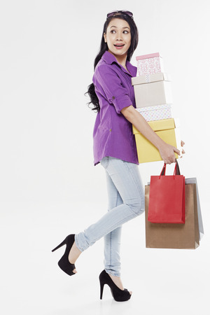Woman carrying a stack of boxes and shopping bags photo