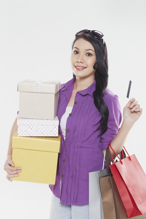 Woman holding credit card and shopping items photo