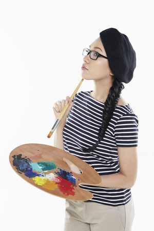 Female artist holding a paint brush and palette photo