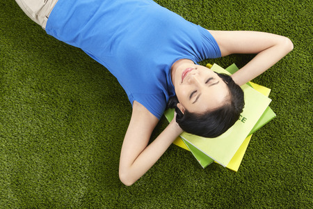 Woman studying while laying on the grass photo