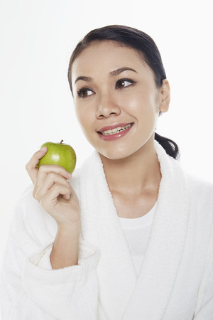 Woman in bathrobe holding a green apple photo
