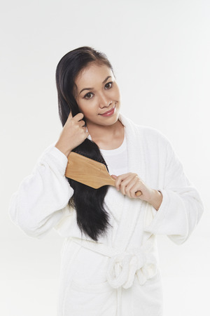 Woman in bathrobe brushing her hair photo