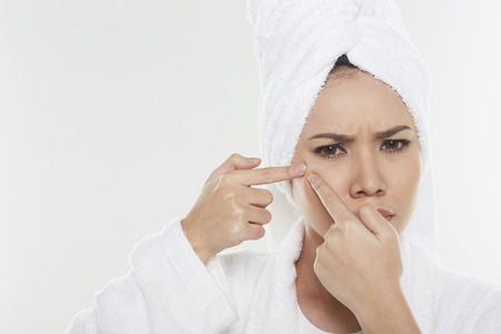 Woman pinching pimple on her face
