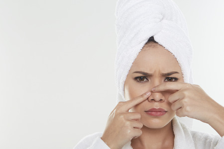 pinching: Woman pinching pimple on her face