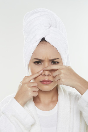 Woman pinching pimple on her face photo