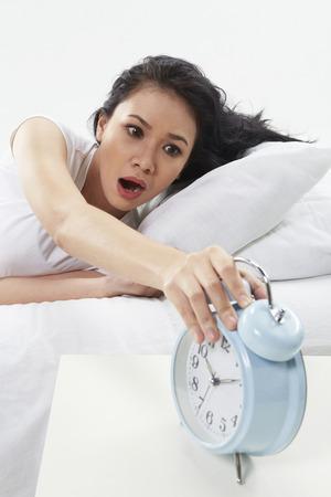 Woman turning off alarm clock photo