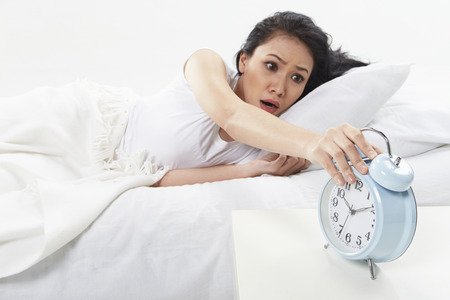 Woman turning off alarm clock photo