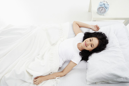 Woman lying on the bed, smiling photo
