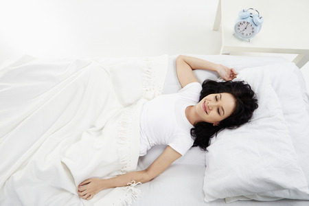 eyes closing: Woman lying on the bed, smiling