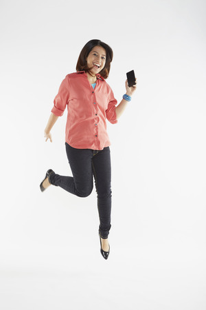 Woman jumping in the air while holding mobile phone Stock Photo
