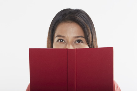 Woman covering half her face with a book photo