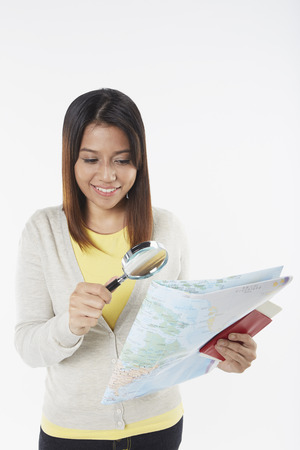Woman looking at map with magnifying glass photo