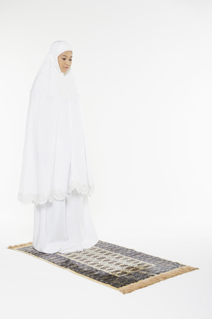 Woman facing the Qiblah with the intention of performing prayer photo