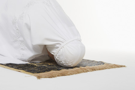 reciting: Woman going down to the floor and prostrate by pressing forehead, placing palms, knees and pads of the toes on the floor