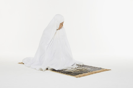 reciting: Woman performing the ending salam, turning face to the left