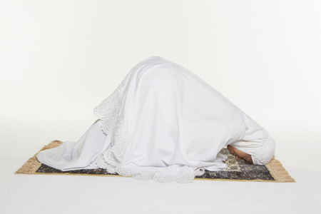 Woman going down to the floor and prostrate by pressing forehead, placing palms, knees and pads of the toes on the floor photo