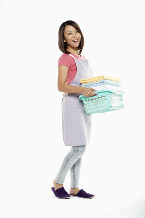 Woman carrying a stack of clean towels