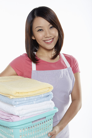 Woman carrying a stack of clean towels photo