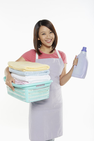 Woman carrying a bottle of detergent and towels