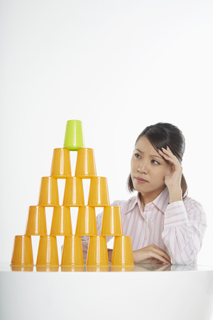 Businesswoman looking at a stack of disposable cups, contemplating photo