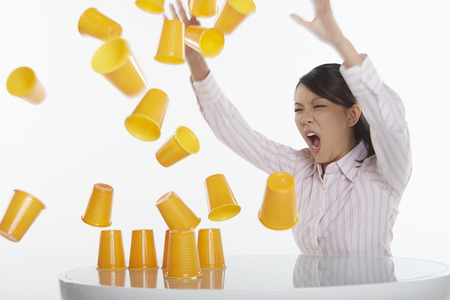 Businesswoman hitting pyramid of disposable cups photo