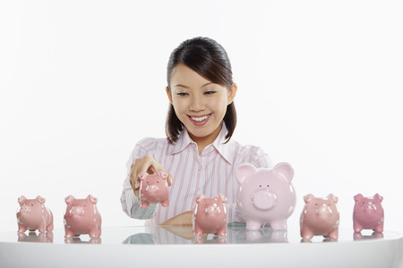 Businesswoman playing with piggy banks photo