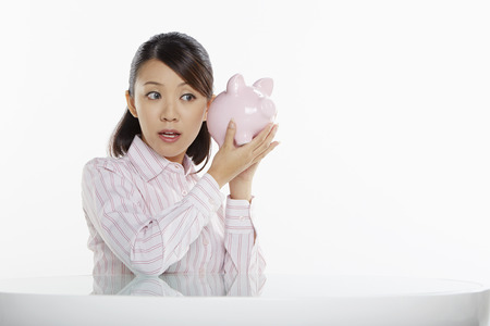 Businesswoman putting ears against a piggy bank photo
