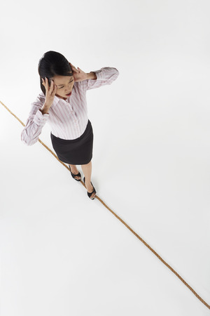Businesswoman walking on a tightrope, stressed photo