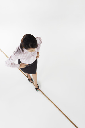 Businesswoman walking on a tightrope photo