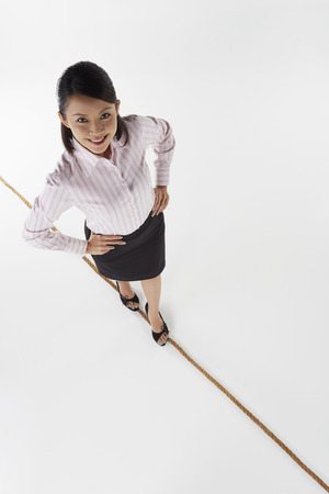 Cheerful businesswoman walking on a tightrope photo