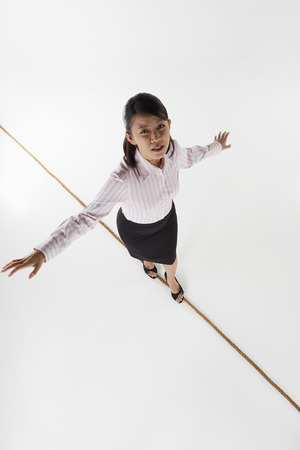 Businesswoman walking on a tightrope, worried photo