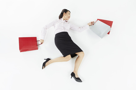 Businesswoman posing on the floor with shopping bags photo