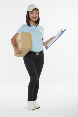 Delivery person carrying a cardboard box and a clip file photo